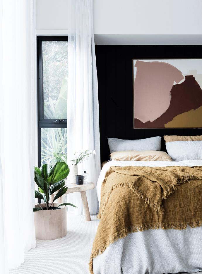 An abstract artwork brings a splash of colour to the bedroom's black feature wall, while sheer curtains pay homage to the room's ample natural light.