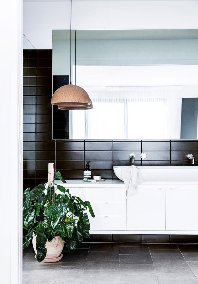 The bathroom mirrors the rest of the home with its black tiled walls, white vanity and sink, grey floors and verdant potted plant.
