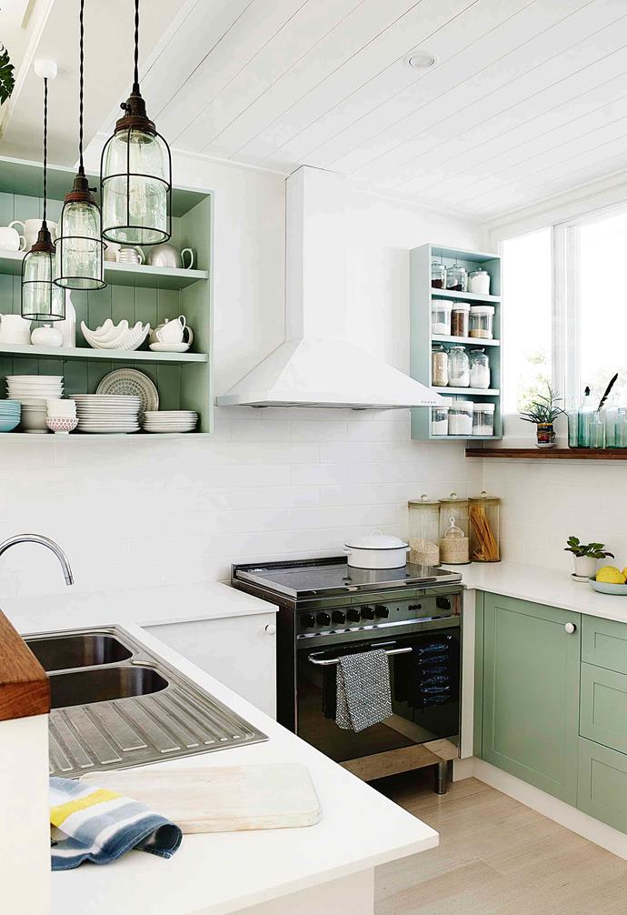 "The kitchen in this [coastal Art Deco-style home](https://www.homestolove.com.au/coastal-art-deco-house-18746|target=""_blank"") proves that subtle splashes of colour is a great way to add style and depth to a small cooking zone. Having the rangehood match the wall colour is a clever way to make bulky items blend into the background."