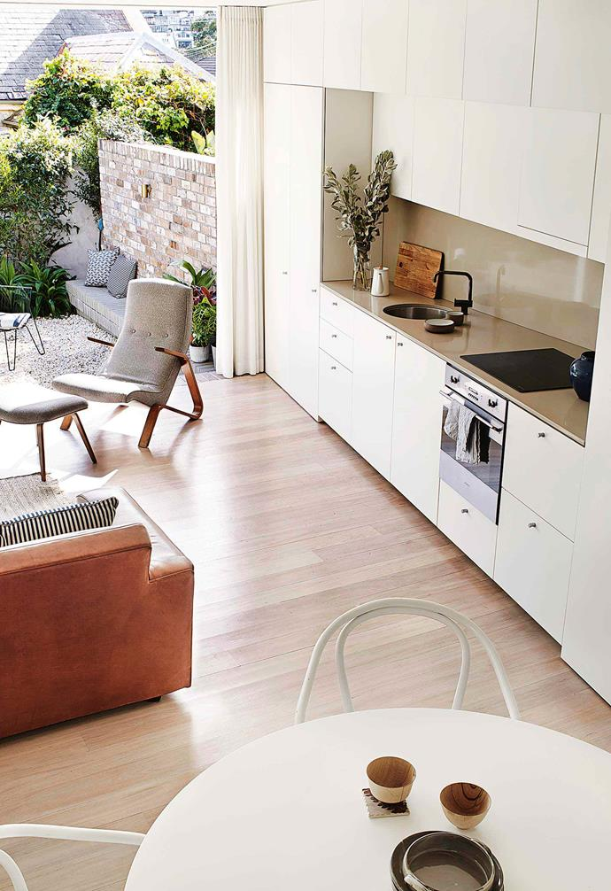 """If your home is narrow, running your kitchen along the length of a wall like this one in this [Balmain home](https://www.homestolove.com.au/multigenerational-living-home-17001 target=""""_blank"""") is a great space-saving option. Sleek cabinetry paired with a glossy bench and splashback creates a modern, seamless look."""
