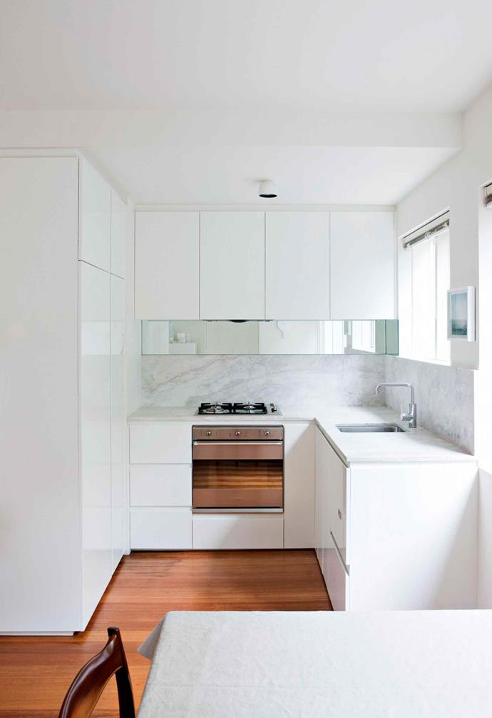 The all-white scheme disguises space constraints, leading the eye smoothly without visual stop-offs. The homeowner took the opportunity to buy quality materials such as the marble benchtops and splashbacks which may not have been financially viable if the kitchen had been large.