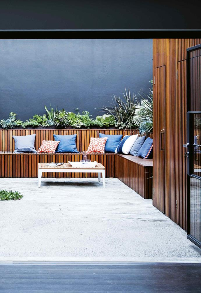 """It's designed to separate the courtyard into two zones,"" says Oliver. ""This creates a kind of barrier between the two areas. The benches are designed for casual lounging, while the table and chairs are a more formal area where you'd sit down for dinner.""<br><br>**Feature wall** The rich textured walls surrounding this garden are painted in Porter's Paints 'Stone Paint Coarse' in Aniseed. The dark tone highlights the organic timber and greenery."