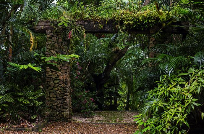 The stone gateway is topped by a hardwood beam planted with orchids, rock lilies, and bromeliads.