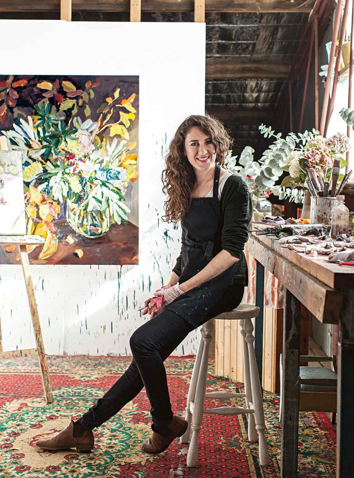 Laura Jones in her studio with one of her paintings, *Banksias and Autumn Leaves 2014*.
