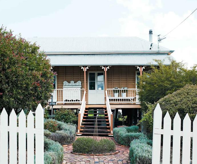 Yellow cottage on stilts with picket fence and tin roof