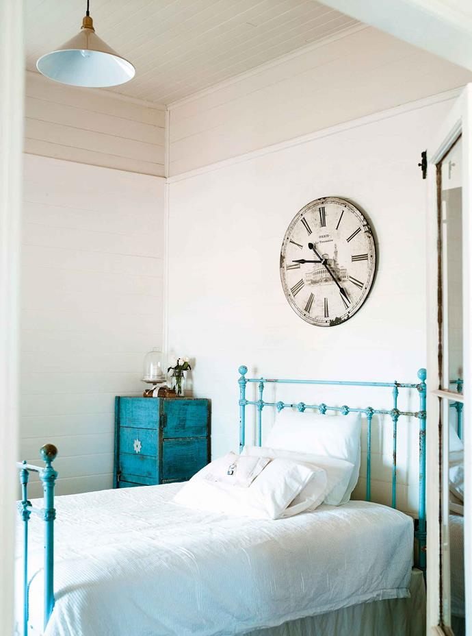 """An iron bedstead in duck-egg blue and a teal-painted chest made from packing cases add colour to the main bedroom. While the three-bedroom cottage is relatively small, the white walls and high ceilings create a spacious feel: """"It's best to have a [neutral background](https://www.homestolove.com.au/diy-guide-to-neutral-colours-5378
