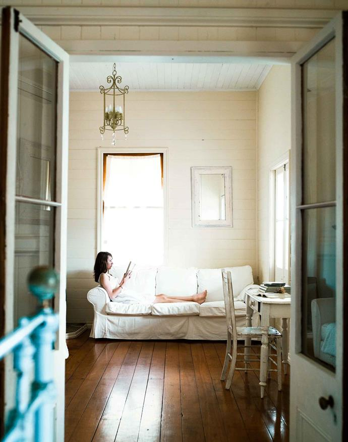 """Cathy's daughter Kirstie relaxes in the living room whose high ceiling increases the impact of light and space. The [railway worker's cottage](https://www.homestolove.com.au/historic-cottage-renovation-13047