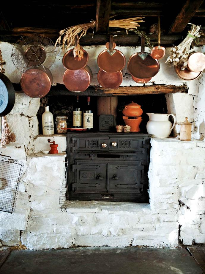 "Copper pans hang above the wood stove. The renovation of Cherry Tree Cottage has kept faith with the original frugal style. When young, time spent at Cherry Tree Cottage was like one long adventure for her three sons and two daughters, and their many friends. ""We always had a boat and went fishing in Coles Bay, which is only 15 minutes away,"" she says. ""And my boys loved motorbikes and used to have all their friends around… it was idyllic."""