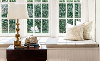 Window seat with a table decorated with antique items