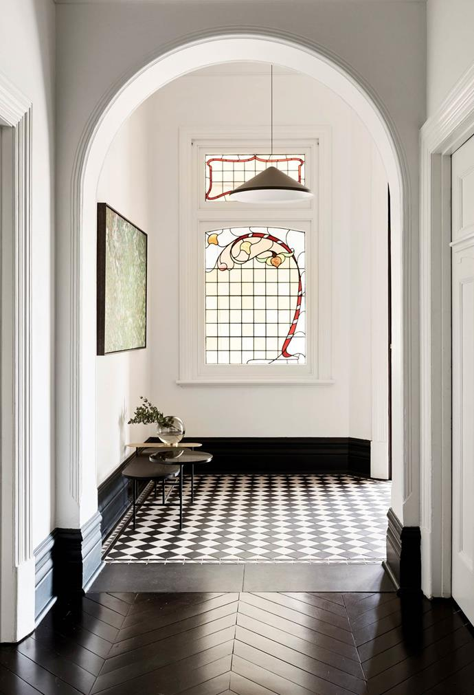 The entry to this Edwardian home that has been updated by architecture firm BayleyWard opens into an inviting reception vestibule with a chequerboard floor and decorative leadlight windows.