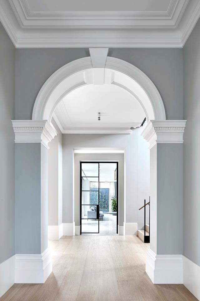 "[Christopher Elliott](https://www.homestolove.com.au/two-storey-victorian-home-with-edgy-interior-melbourne-19201|target=""_blank"") seamlessly combined the existing heritage features with an expansive new extension. In the hallway, the original Victorian arch leads to a glass steel door that opens onto the home's new addition."