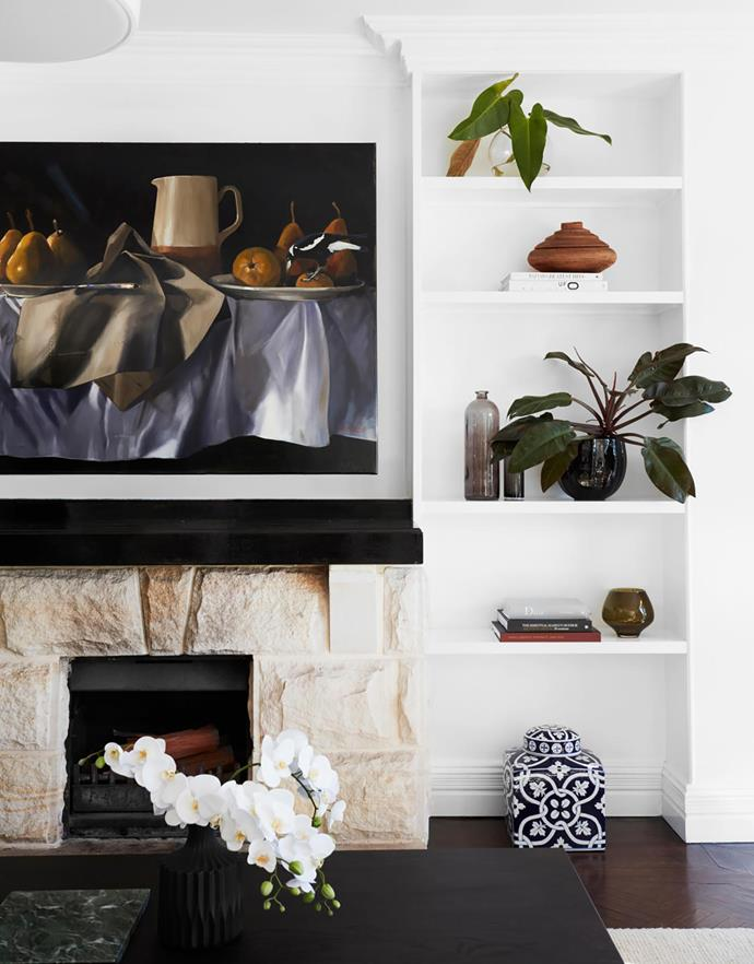 """The sandstone on the living room fireplace was retained, a nod to the nearby beach. """"It's simple and elegant, not overwhelming,"""" says Michelle. Artwork by Diana Watson."""