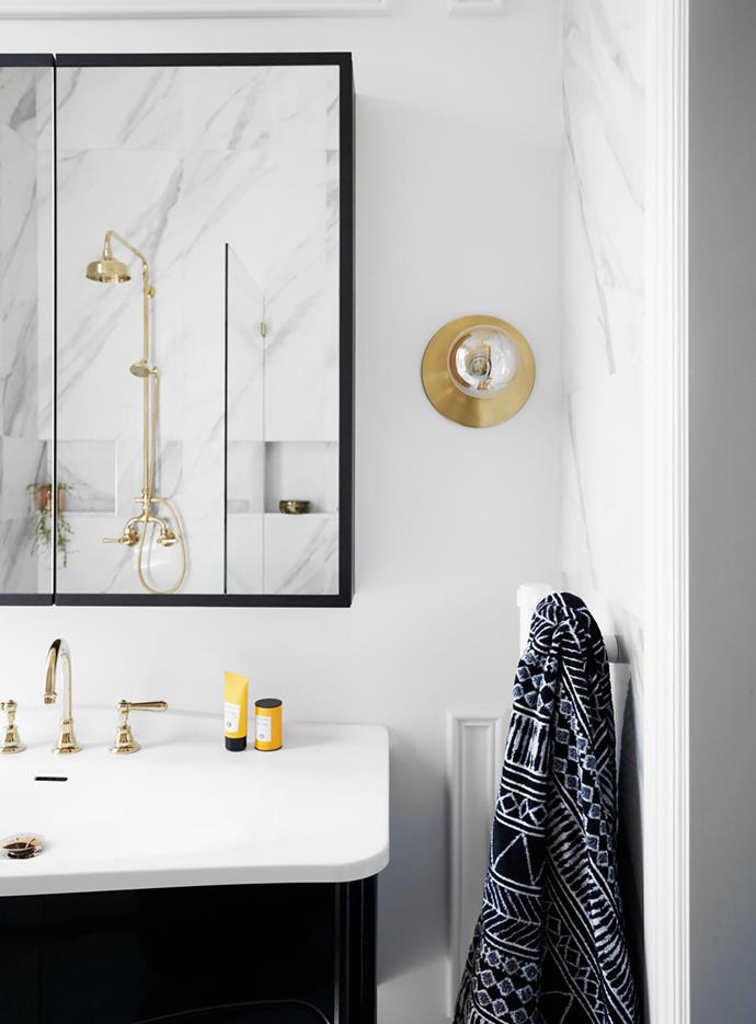 Gold accents deliver luxury and warmth in the monochrome scheme. Bianco Carrara marble wall and floor tiles, Tile Mega  Mart. Victoria+Albert 'Mandello' vanity, Reece. Neu England tapware, Brodware. Lord wall sconce, Catapult Design.
