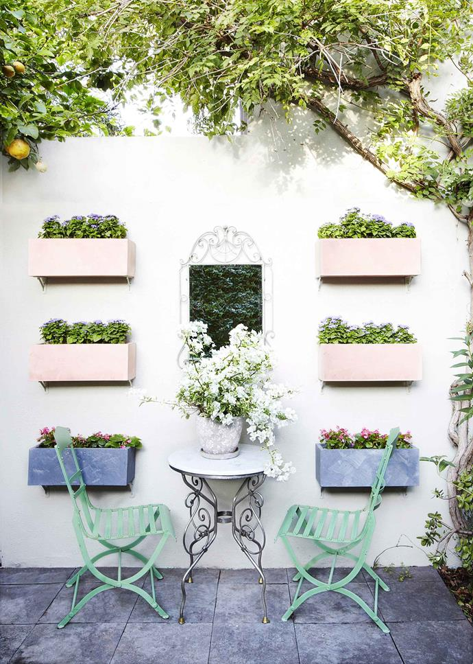 Wall mounted planters painted in pastel shades lend this balcony a Parisian air.