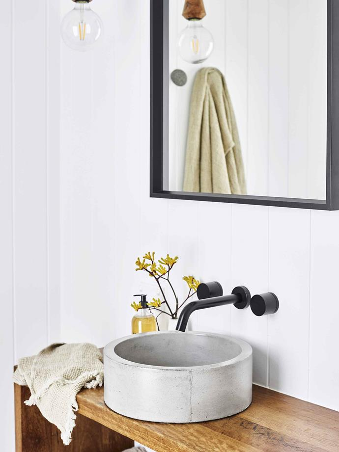 Prepare the guest bathroom by adding a set of towels and a flower arrangement.