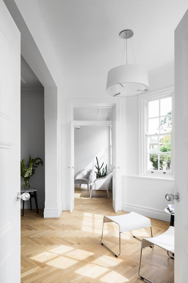 "A pure white treatment breathes air into this [art deco apartment](https://www.homestolove.com.au/woollahra-apartment-by-marston-architects-5618|target=""_blank"") in Sydney's eastern suburbs that has been re-imagined by Marston Architects. European oak herringbone floors provide warmth to the home."