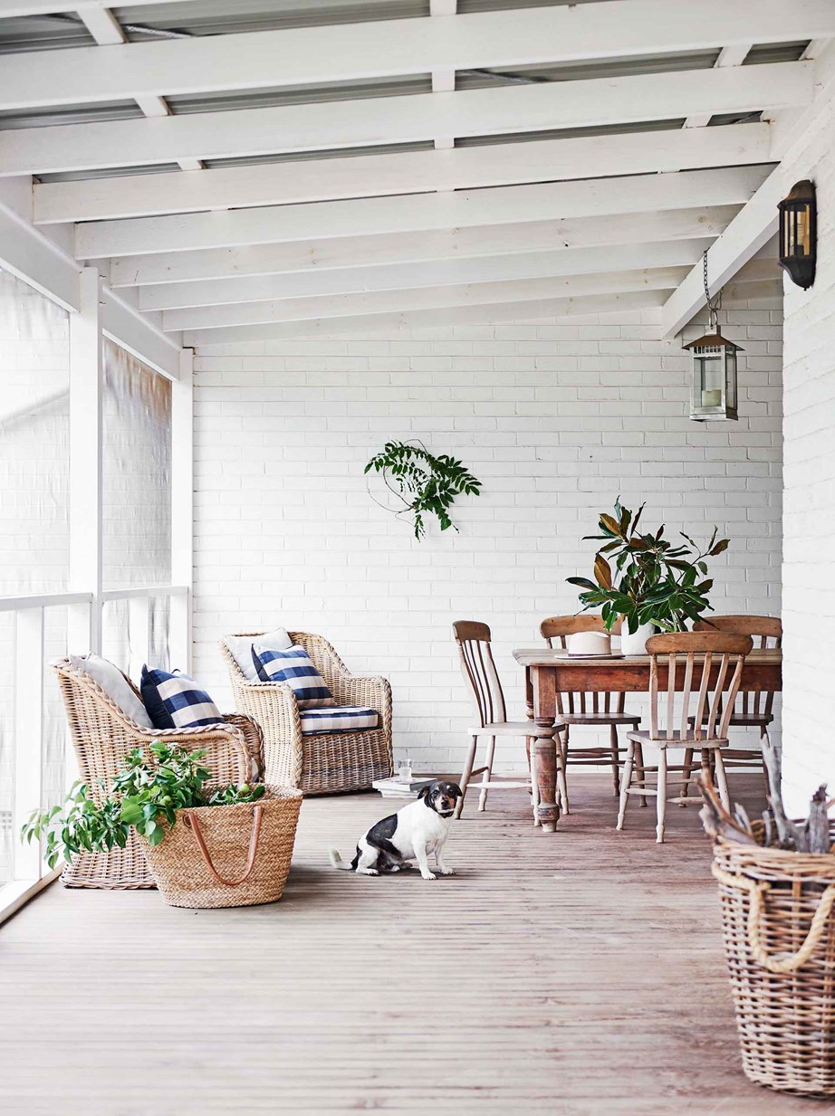 "On the large wraparound verandah is where the owners of this white [farmhouse with a modern interior](https://www.homestolove.com.au/modern-farmhouse-interior-20719|target=""_blank"") like to entertain and where Max the Jack Russell spends most of his time waiting for pats or treats under the table."