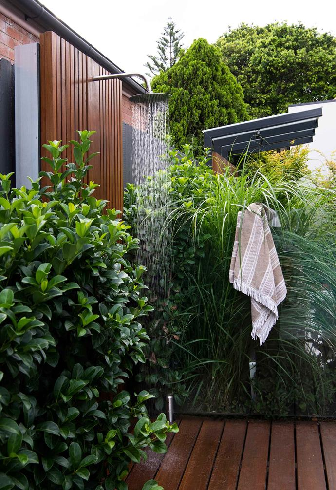 **Outdoor shower** The large garden is divided into many different zones, differentiated with new timber screens, decks and built-in furniture that complement the brown-brick Arts and Crafts-style Federation home. A lush mix of pleached trees, groundcovers and layered plantings surrounds the poolside shower, which has a luxurious rainforest feel the owners love.