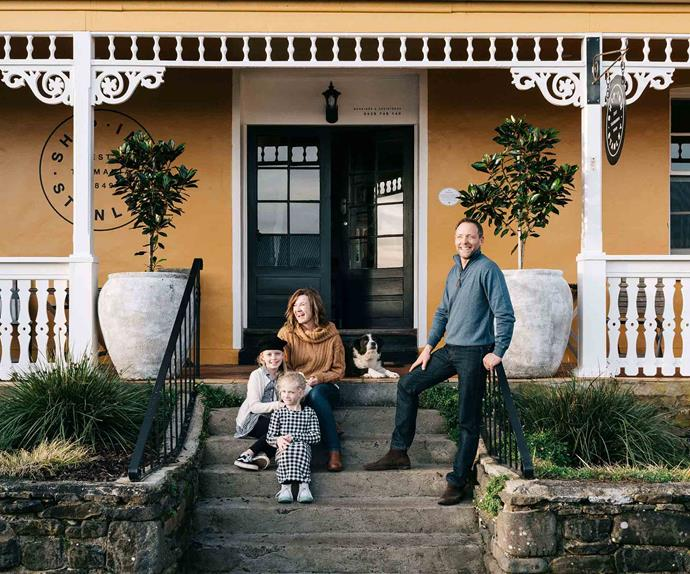 Family sitting on front steps of a yellow house
