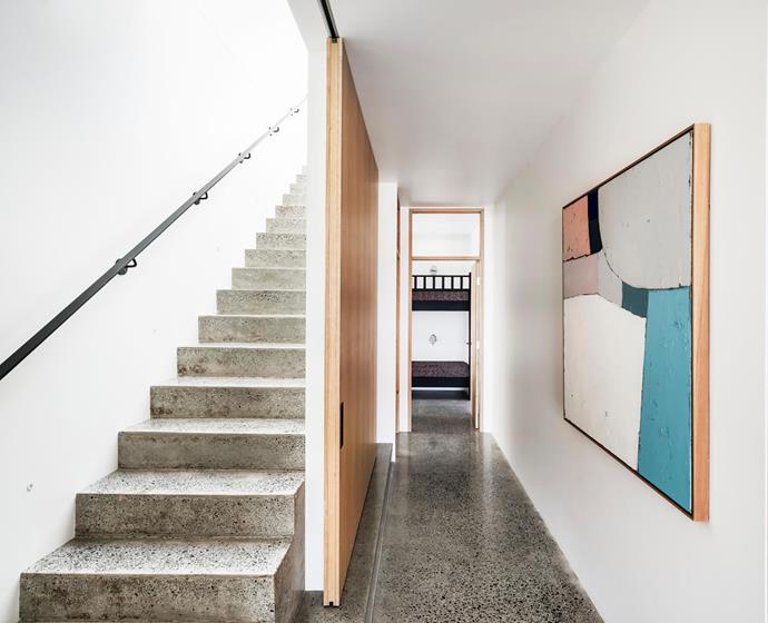 Polished concrete floors connect interior and exterior spaces. In the hallway hangs Farrah by Middle of Nowhere from Life Interiors.