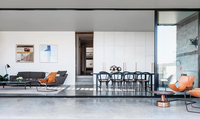 Strategically placed windows ensure the entrance gives few clues about the home's interior. Objekto 'Paulistano' leather and steel armchairs from Hub. Thonet 'No. B9' dining chairs in Black. Gubi 'Grasshopper' floor lamp. Photographs by George Byrne are from Olsen Gallery.