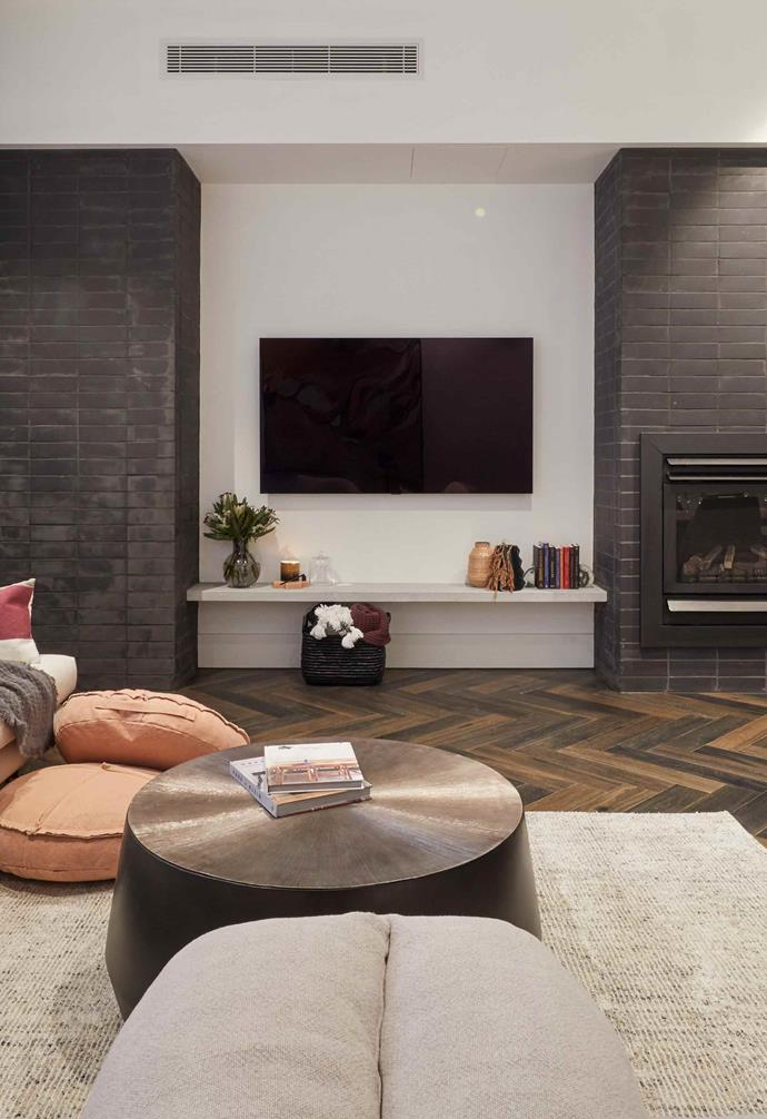 "**Week 8, Living and Dining** In the [open-plan living area](https://www.homestolove.com.au/the-block-2019-living-and-dining-room-reveals-20694|target=""_blank"") Tess and Luke used dark bricks to clad the fireplace and create a dramatic visual feature. A textured neutral rug is paired with a plush sofa and two armchairs to create a cosy living zone."