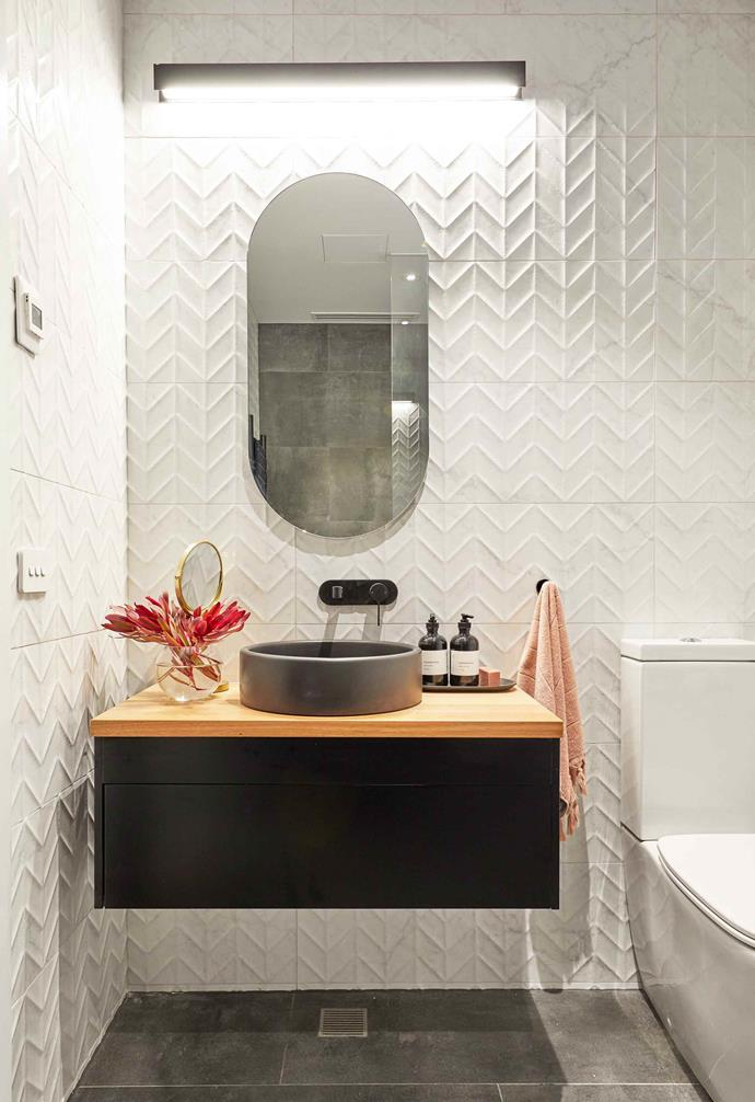 **Week 10, Studio** The bathroom features textured wall tiles, their signature concrete basin and a timber-topped vanity with dark cabinetry.
