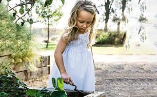 Girl with trowel in vegetable garden