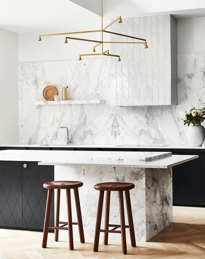 Material contrasts and strong forms play off each other in this monochrome kitchen. The dreamy Laverna marble softens the darker joinery while the brass details add the final romantic touch.