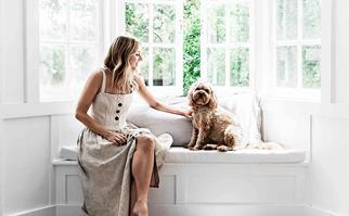 Woman sitting on window seat patting a dog
