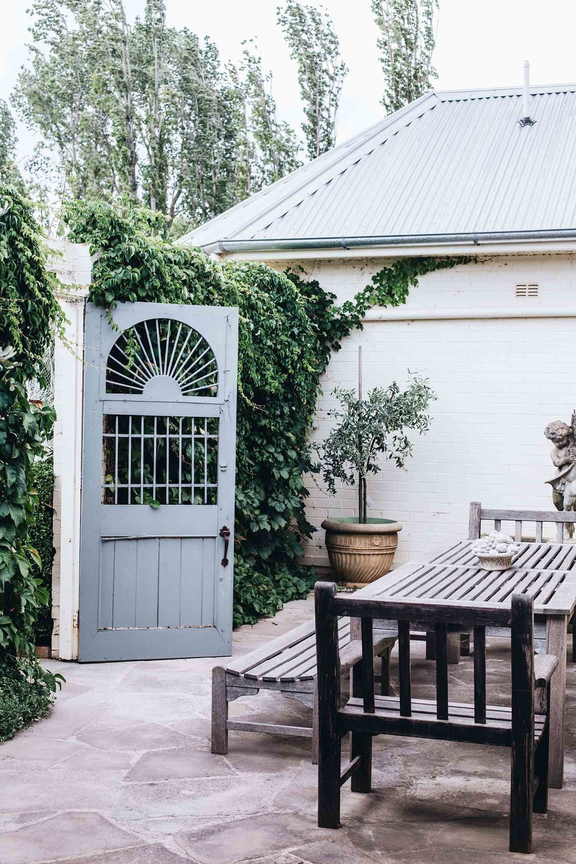 """After working on the farm all day, friends and family often pile in the back of the ute to enjoy a picnic outdoors in the paddock, or in this European-inspired outdoor courtyard with ivy-covered walls, at this [farmhouse in Boorowa, NSW](https://www.homestolove.com.au/boorowa-nsw-farmhouse-20756