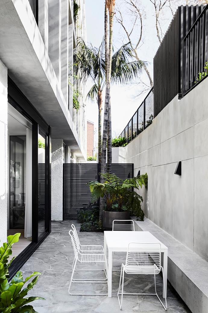 The concrete-rendered facade is softened with climbing plants and palm trees.