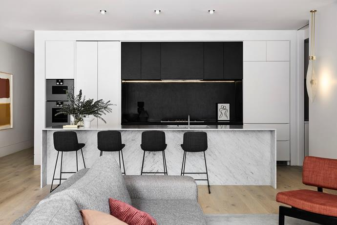 Handle-free jet-black cabinetry looks sleek, and contrasts with the white marble island.