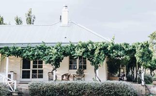 White farmhouse with a wraparound verandah
