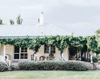 White farmhouse with a wraparound verandah