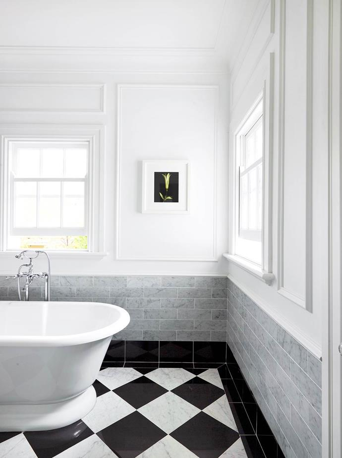 "A freestanding bath takes pride of place in this [serene ensuite](https://www.homestolove.com.au/gallery-emma-and-tonis-luxurious-regency-style-home-2311|target=""_blank"") while panelling creates visual interest on the white walls."