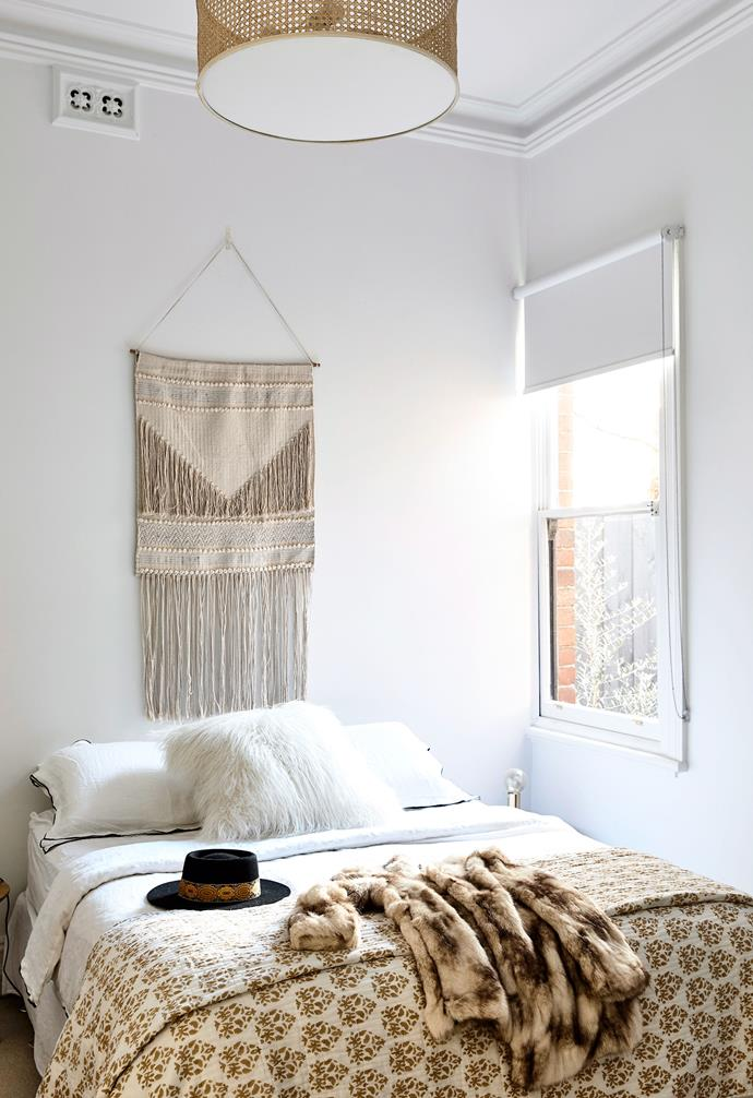A tactile macrame wall hanging takes the place of a traditional bedhead in this compact bedroom.