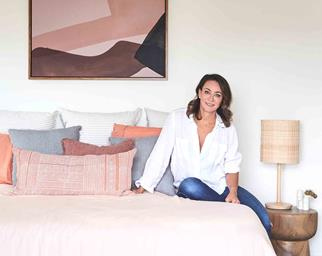Michelle Bridges sitting on a pink bed