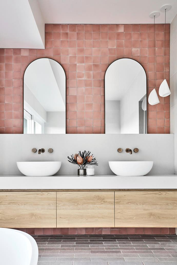 """**Louise Walsh and Kelly Taylor - Louise Walsh Interior Design** <br> When Louise and Kelly sat down to draw up this Northern Rivers NSW bathroom, they had a clear starting point: pretty dusty-pink encaustic tiles. """"The owners wanted a fun and fresh bathroom for their two young daughters; the warm, textural and feminine tiles were perfect,"""" says Louise. Beautiful symmetry underpins this room, with a pair of brass-framed mirrors playing a starring role. """"Their curves lend a playfulness to the space,"""" she says. The Kado 'Lussi' basins and Brodware 'Halo' taps echo the curves of the mirrors and break up the vanity and splashback. Tumbled limestone floor tiles tie the elements together"""