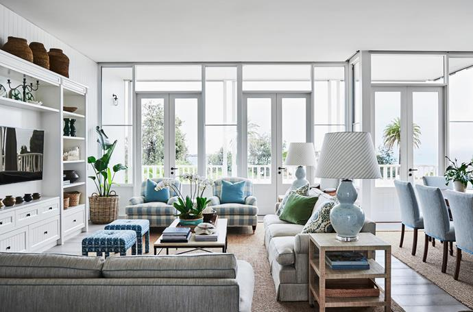 """**Adelaide Bragg - Adelaide Bragg & Associates**<br> This inviting living room in Melbourne lives and breathes its breezy beachside location. """"With a completely blank canvas, it was possible to ensure the design and decorating of the living room and dining room made the most of the home's ocean views,"""" says Adelaide. """"The home is architecturally strong, with floor-to-ceiling glass and views to the bay."""" she says. The bleached palette and driftwood textures, including the wall of white joinery, tongue-and-groove panelling, limed timber floors, cane baskets and sisal flooring bring the beach into the room."""