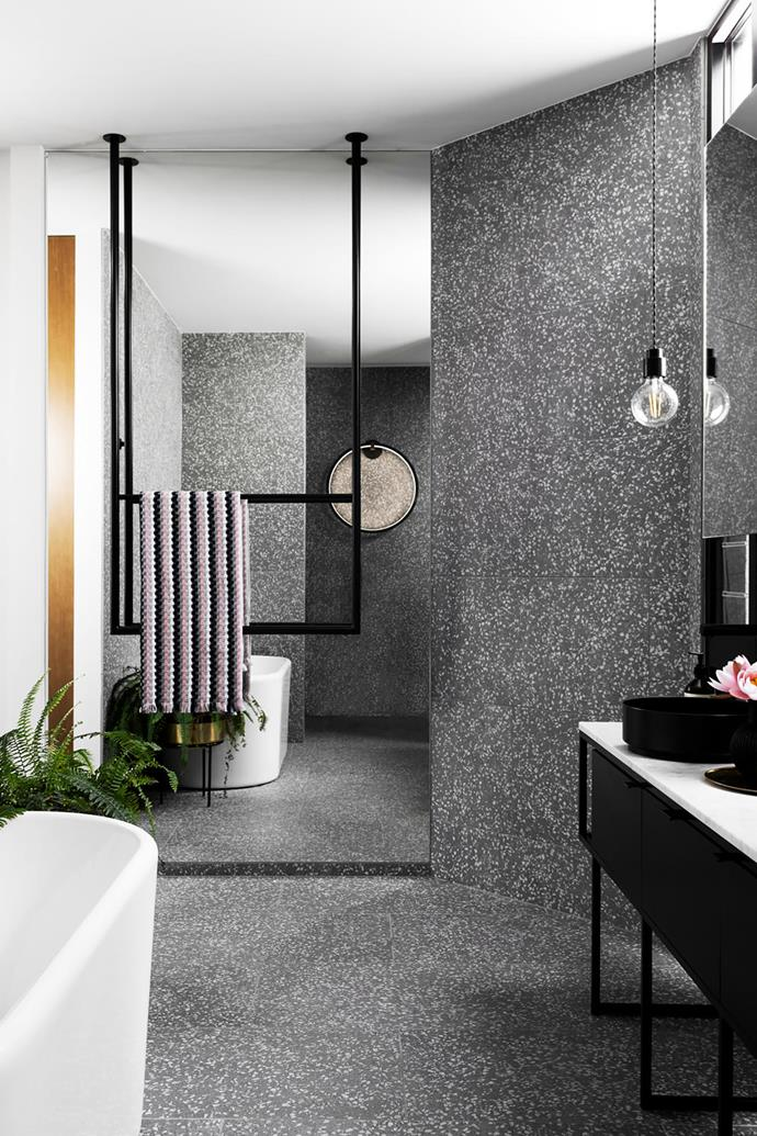 """**Amanda Lynn - Amanda Lynn Interior Design** <br> Simplicity can be utterly luxurious, as this artfully restrained Melbourne bathroom proves. The L-shaped space wraps around a lush courtyard and is designed to allow its materials to shine. The repetition of terrazzo-look tiles and black steel ensures the space is ordered and serene. A custom-made steel towel rail is an inspired inclusion, as is the black-framed Aeon Hardon wall light. """"The light is a subtle focal point in the room,"""" says Amanda. She has deftly combined sharp lines and rounded shapes to deliver a bathroom the owners are delighted with: """"We love the sense of spaciousness and the fact that the shower is open to our private courtyard""""."""