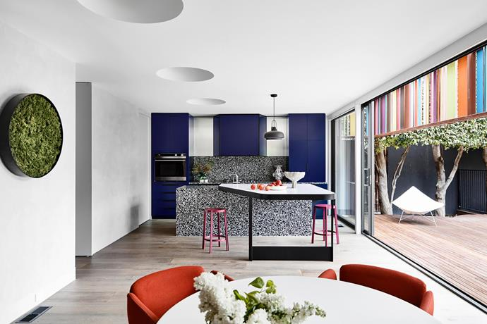 """**Mardi Doherty - Doherty Design Studio** <br> This Melbourne home has a colourful past – quite literally. So when the team at Doherty Design Studio took on the task of updating its kitchen, they were determined to honour its vibrant renovation, completed in 2000 by Kennedy Nolan. """"Rather than shunning its retro elements, we heartily embraced them,"""" says Mardi. Bold joinery in Dulux Gentian Violet is teamed with a gorgeous terrazzo island and splashback, and bright seating. """"The new kitchen/dining space has improved flow and connection to the garden,"""" says Mardi. """"The home's retro past can still be enjoyed. It just  feels more modern."""""""