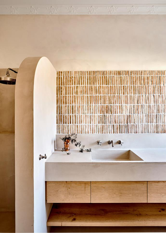 """**Georgia Ezra - Studio Ezra** <br> Tactile in every element and creatively executed, there's a clear Mediterranean influence in this ensuite in Georgia's own home. A curved nib wall separates the shower from the vanity, while the Marius Aurenti render softens the effect of the monolithic benchtop and walls. Moroccan bejmat tiles were laid vertically, spaced widely for full impact: the effect piques curiosity and provides visual softness. Georgia says she looks at design holistically: """"Spaces affect our senses, spirit and mood. Here, we wanted a practical and functional design that also emulated beauty and a strong feeling of escape""""."""