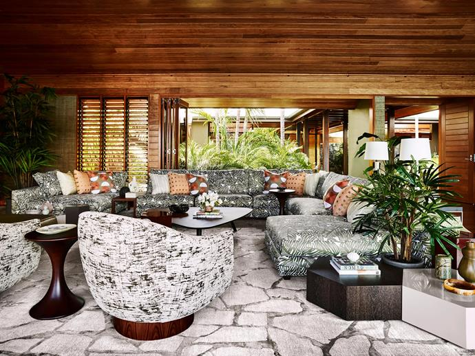 """**Greg Natale** <br> While this living room on Hamilton Island was inevitably laidback, the owners wanted it to evoke city-cool too. """"As much as this was a holiday retreat, comfort and luxuriousness were always paramount for my clients,"""" says interior designer, Greg Natale. """"They love Italian furniture, so we used predominantly Minotti pieces."""" Indeed, Minotti's Maui fabric was the starting point for a scheme that beckons the outdoors in in a luxe, glamorous way. Timber, lush foliage and bold organic patterns evoke a seductive tropical languor, but the black-and-white palette and elegant furniture profiles add a smart uptown twist."""