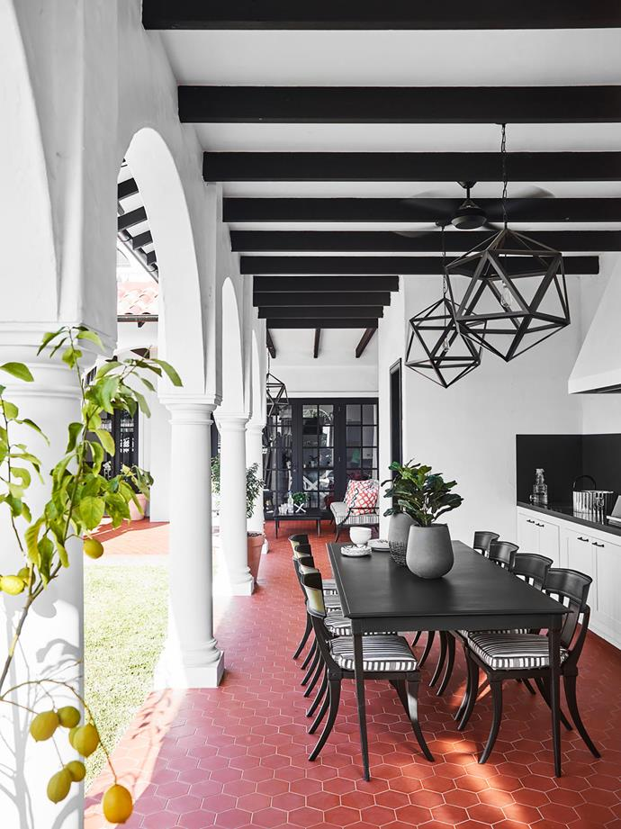"""**Greg Natale** <br> A brief for Spanish Mission-style design and comfortable indoor-outdoor spaces layered with soft furnishings produced this grand new home in Sydney's west. For this alluring loggia, Greg drew inspiration from classic Spanish Mission design, executed with black beams contrasted with white render, terracotta floor tiles, fans and upholstered outdoor seating, together with an outdoor kitchen, all flanked by an elegant colonnade. Keen entertainers, the family use the space all year round. """"I love the earthiness of the terracotta tiles, a hallmark of Spanish Mission style – they set the tone for the whole space,"""" says Greg. """"I really liked exploring earthy textures and tones, which isn't something I do often."""""""