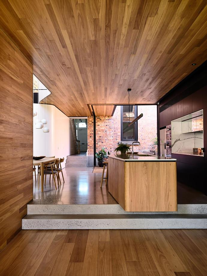 """**Matt Gibson & Karen Batchelor Matt Gibson Architecture+Design** <br> Raw, tactile materials and an interplay of intriguing shapes are the hallmarks of this newly extended Victorian terrace in inner-city Melbourne. At the heart of the elongated open-plan zone is the kitchen. And central to the kitchen is the sculptural island bench, which cantilevers over the steps, with one end dedicated to sink/food prep and the other to meals. """"The curvature of the island echoes the curved and arched elements of the original house,"""" says architect Matt Gibson. The island is clad in oiled blackbutt – the same timber used to line the ceilings and wrap the wall – while the floor is burnished concrete. """"The kitchen offers all the storage and functional needs for a family of five, while featuring a rich and textured materiality that weaves into the story of the original house,"""" says Matt."""