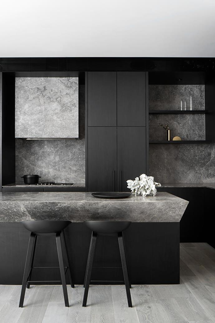 """**Ben Robertson - Tecture** <br> The owners of this Melbourne kitchen sometimes have to pinch themselves when they walk into it. The shark-nose detailing on the island bench is striking, but the hero is the mottled Grey Aether marble itself. The developers of this townhouse asked Ben to draw up spaces that were luxe yet still within a strict budget. """"The island bench takes its shark-nose edge to the maximum, making it a very prominent feature,"""" says Ben. Setting the marble against intense matt-black veneer is a stroke of genius; it frames the stone spectacularly and highlights the deeper tones in its veining. An integrated fridge is located in the centre of the space. """"It's placed there to break the lines up and make the kitchen appear larger,"""" says Ben."""