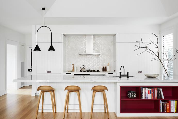 **Lauren Li - Sisällä** <br> This Edwardian home in Melbourne, extended in the mid 1990s, desperately needed a design update – especially in the kitchen. Lauren extended the existing island bench to the wall, allowing for an under-bench wine fridge, and installed new cabinetry, appliances and lighting. The ruby red storage was inspired by an artwork with matching tones in the owners' treasured collection; the cabinet handles are colour-matched to the shelving. Tactile handmade Moroccan tiles on the splashback are another standout feature, delivering subtle texture. It's now a great entertaining space, which the sociable owner loves.