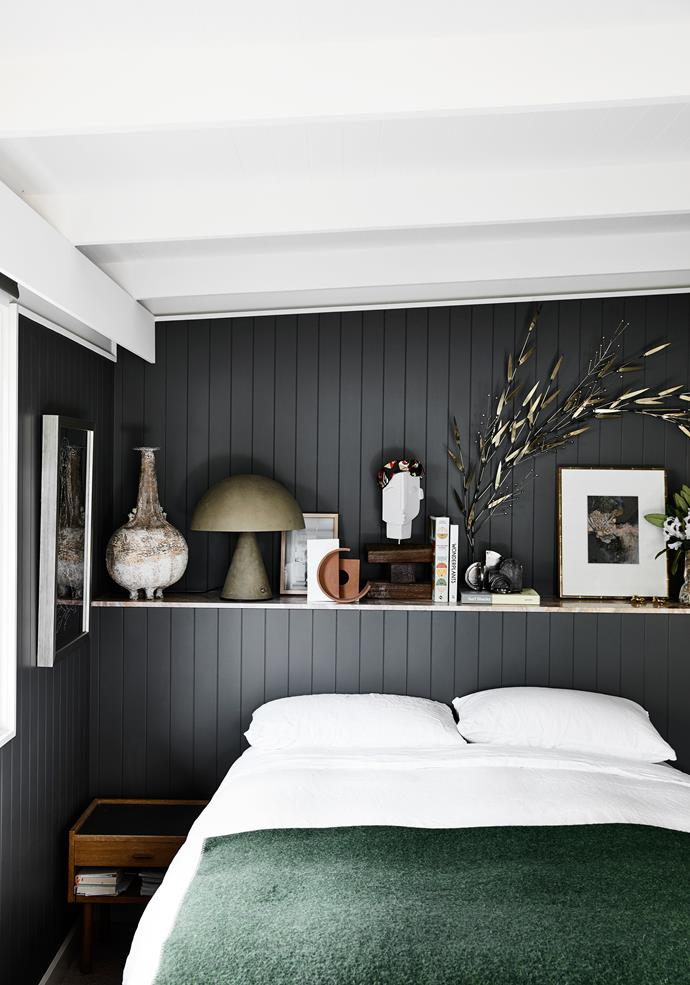 "Simone wanted to create a fun but moody feeling in the master bedroom. [Dark walls](https://www.homestolove.com.au/best-dark-paint-colours-20169|target=""_blank"") work as a backdrop for warm metallics, quirky sculptures and a vibrant green bedspread. The bedlinen is from Abode Living, with shelves holding objects including a Nicholas & Alistair lamp, Jane McKenzie ceramic and Curtis Jere sculpture."