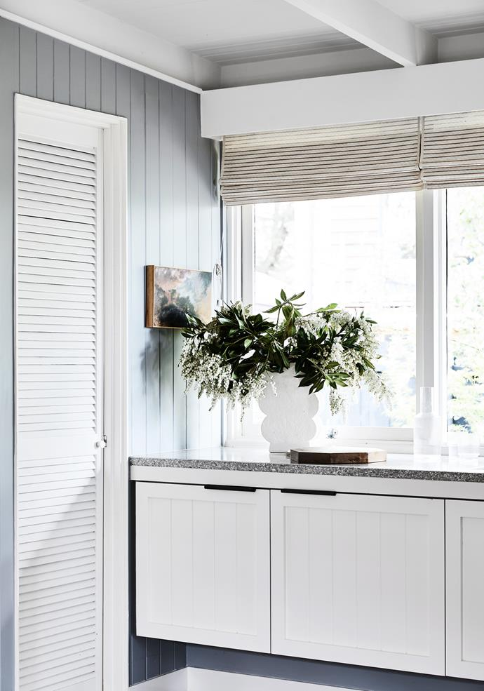 Kitchen cabinets were custom made to match the wall panels, with the doors painted Haymes Organic 1 white. Simple roman blinds let in plenty of light.